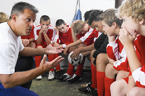 A male sports coach squats down to huddle up with his team and strategize.