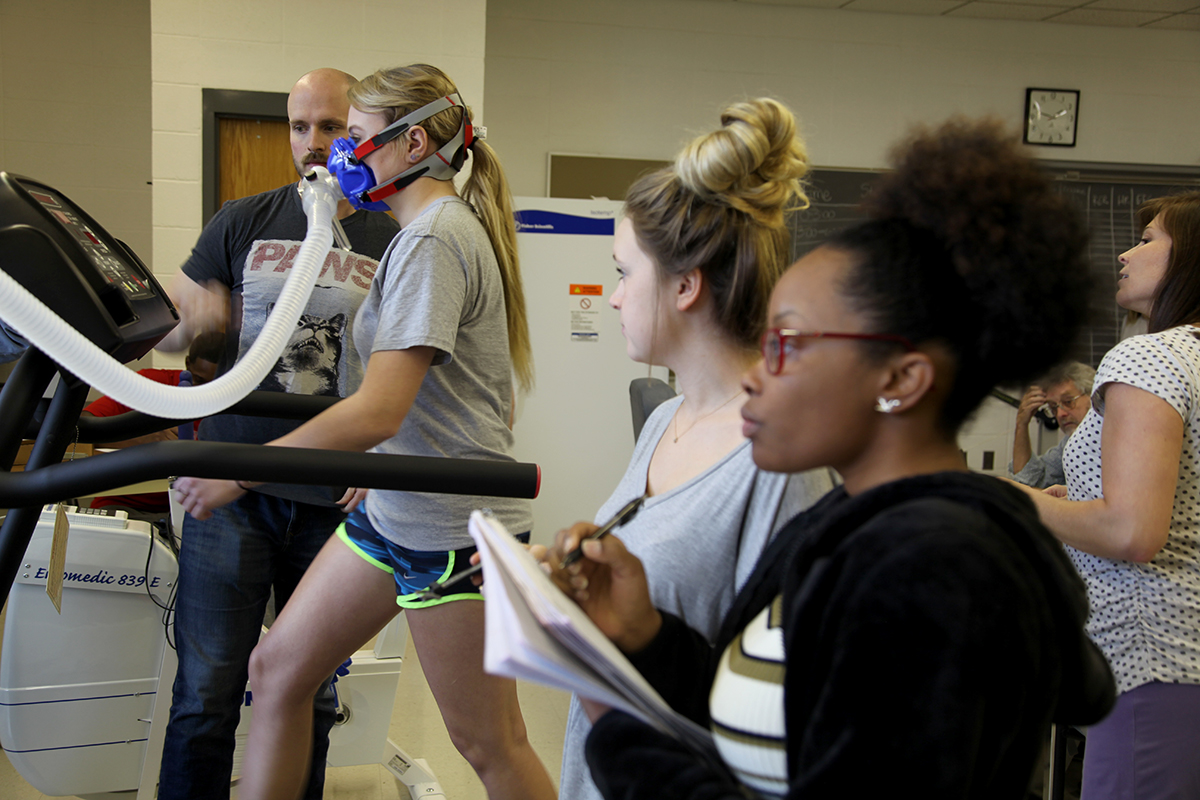 Kinesiology students measure respiration rate and blood oxygenation for a runner on a treadmill.