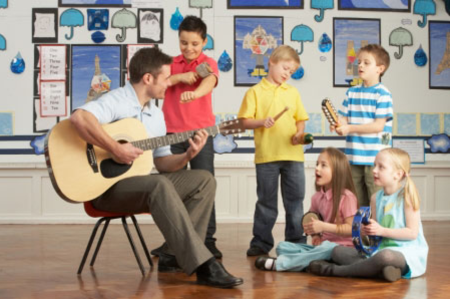 A male teacher accompanies elementary school singers by playing a guitar.