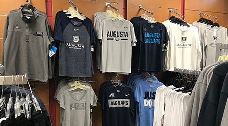 Augusta University branded shirts hanging on a wall