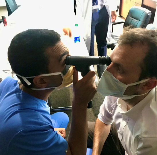 Resident giving eye exam