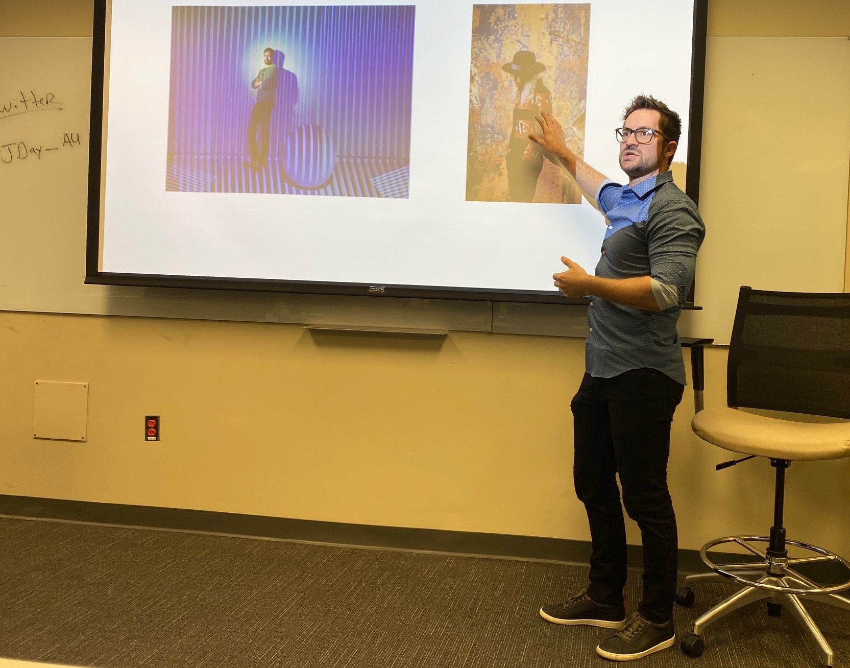 Professor Dylan Wilson points to two photos as he teaches photojournalism class