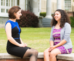 Ana Merloiu and Christie Sanchez, two students at Augusta University, sitting on a bench outside of Allgood Hall