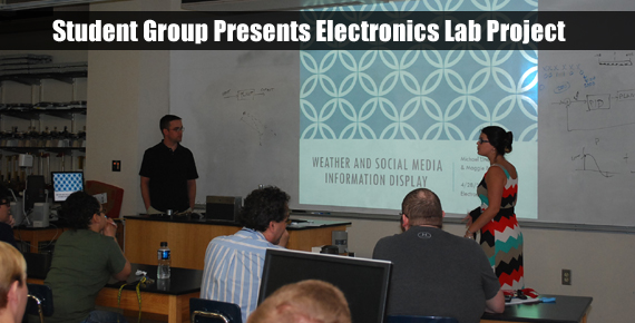 Two students standing in front of a projection screen as they present their Electronics lab project to an audience