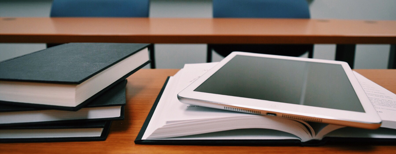 closeup of books and an electronic tablet on a table inside a classroom